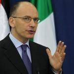 enrico letta con la mano destra in alto ed il palmo aperto con dietro una bandiera italiana