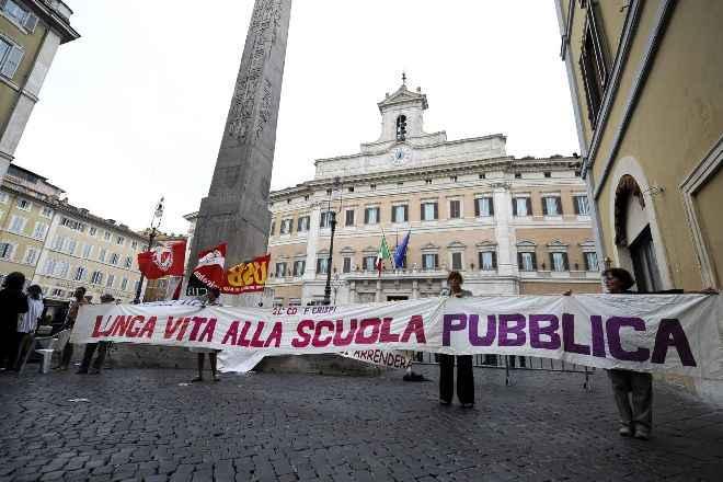 """Un gruppo di manifestanti davanti a Montecitorio reggono uno striscione con scritto """"lunga vita alla scuola pubblica"""""""