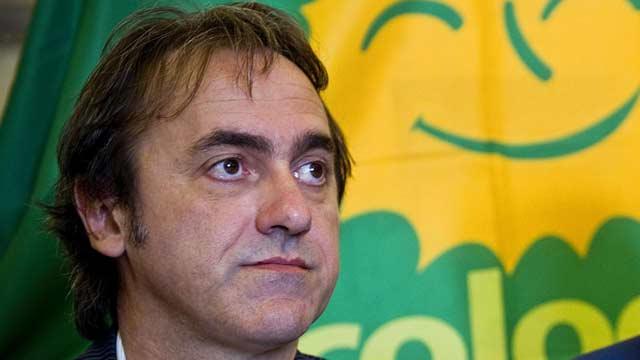 Primo piano di Angelo Bonelli con la bandiera dei Verdi sullo sfondo