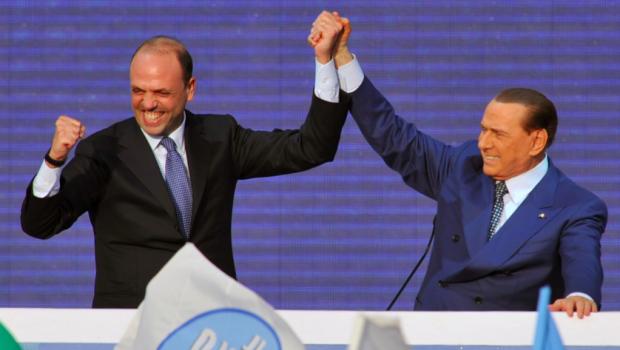 berlusconi e alfano mano nella mano sul palco con espressione di gioia