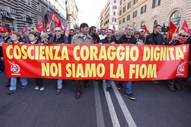 """Un gruppo di manifestati sfila in una via di una grande città. Reggono uno striscione in cui si legge """"scienza coraggio dignità noi siamo la Fiom"""""""