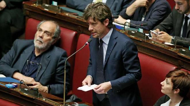 Pippo Civati in parlamento con foglio in mano parla al microfono.