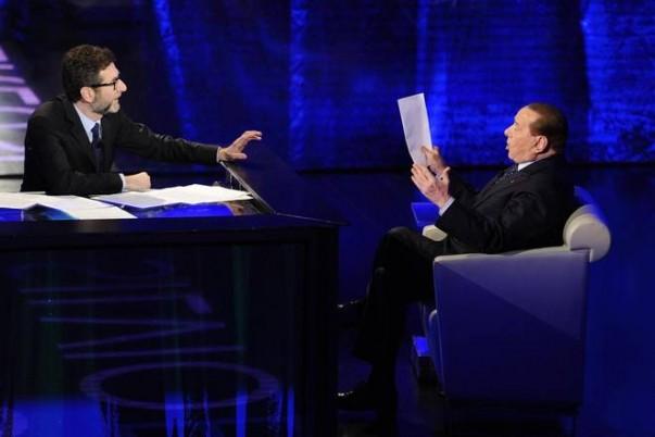 Silvio Berlusconi viene intervistato nello studio di che tempo che fa da Fabio Fazio. Fabio Fazio è seduto davanti ad una scrivania con la mano protesa verso Berlusconi. Berlusconi è seduto in poltrona e regge dei fogli.