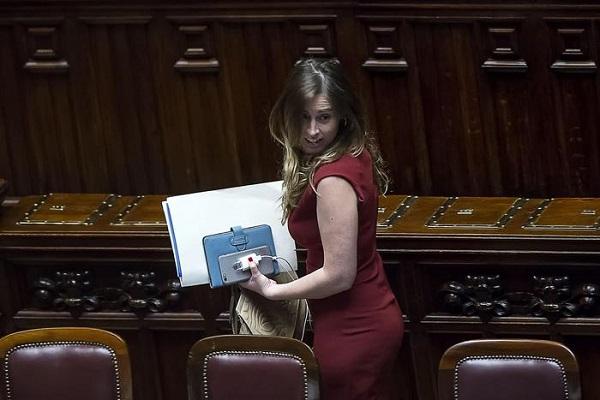 Il ministro Maria Elena Boschi con tabelt e appunti si allontana daii banchi del governo con vestito rosso e guarda verso il suo lato sinistro