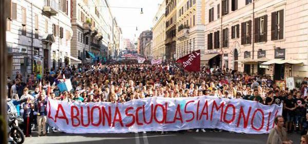 Una folla di manifestanti sfila nella via di una città. Reggono uno striscione con scritto: la buona scuola siamo noi