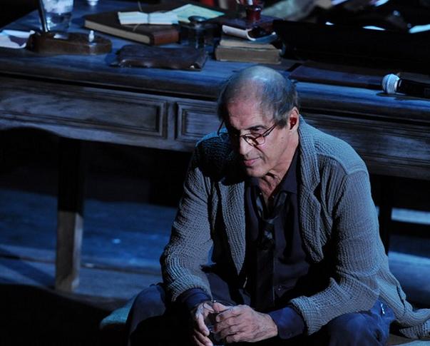 celentano seduto sulla scena durante un suo spettacolo