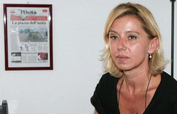 l'ex direttrice de l unita de gregoria in maglia nera seduta con lo sfondo di una copertina del giornale incorniciata