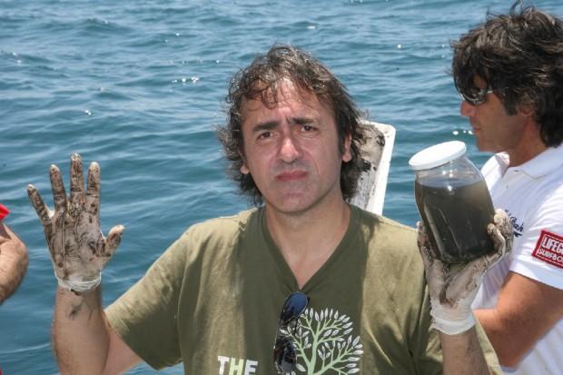 Angelo Bonelli su una barca in mare a braccia alzate. Nella mano sinistra regge un brattolo contenente liquido nero