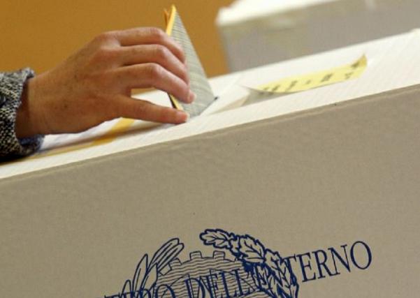 il momento del voto con elettore che inserisce la sua scheda nell'urna