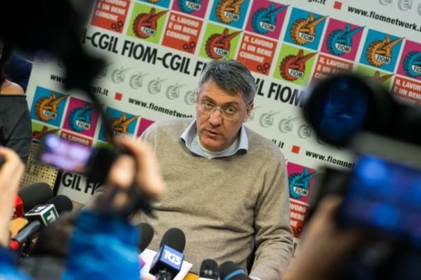 Maurizio Landini intervistato dalla stampa, sullo sfondo i simboli di Fiom e Cgil