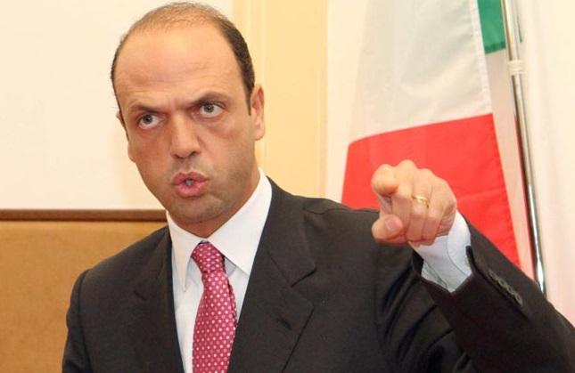 alfano con cravatta rosa e mano sinistra alta con indice alzato su sfondo bandiera italiana