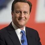 in foto il vincitore delle elezioni in gran gretagna david cameron con cravatta blu e sullo sfondo la bandiera inglese