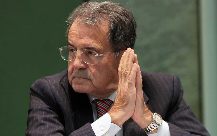 Romano Prodi con le mani giunte guarda alla sua destra