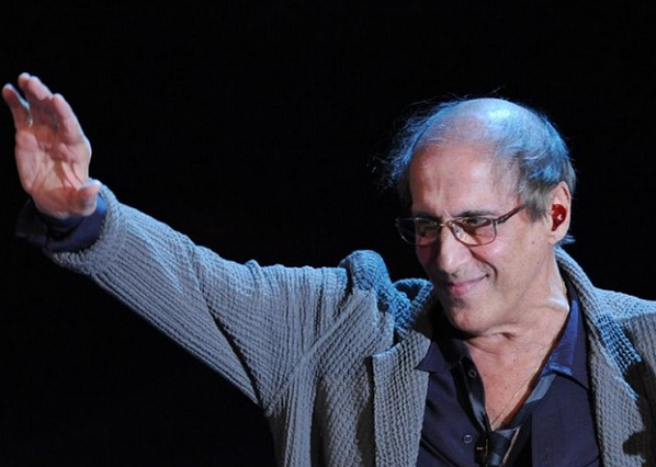 adriano celentano saluta pubblico durante uno spettacolo alzano la mano destra