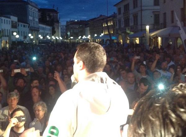 salvini sul palco parla durante un comizio indossando una felpa bianca.