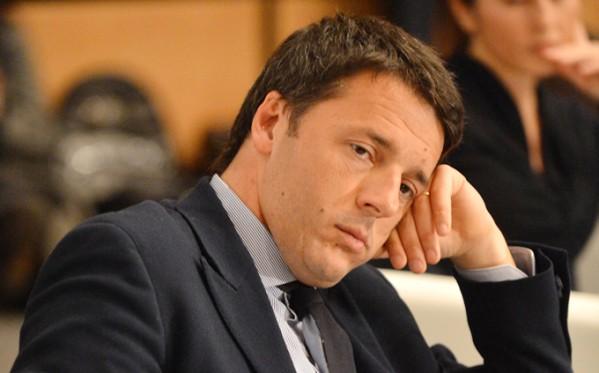 Matteo Renzi in giacca e cravatta la testa appoggiata sulla mano, aria sconsolata