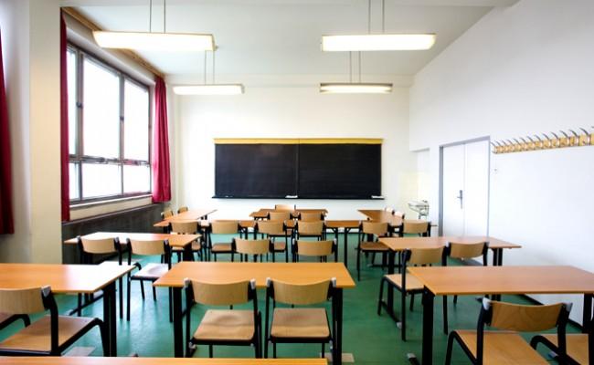 immagine di un aula di scuola, la lavagna in fondo e in mezzo file di banchi e sedie.