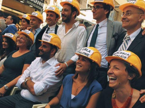 foto sindaco di bari e suoi assessori durante la presentazione della giunta con caschi gialli da lavoro in testa e cognome scritto in nero su foglio bianco poggiato sul casco