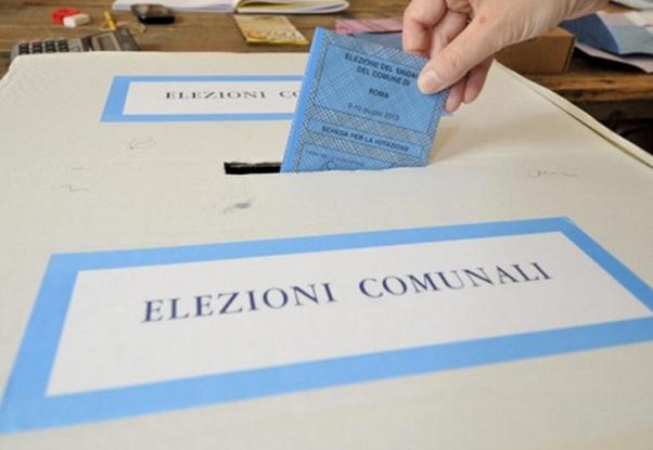 elettore al voto mentre inserisce scheda nell'urna elettorale
