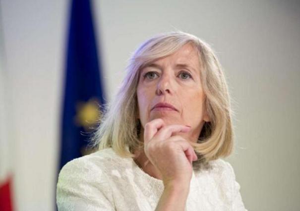 ministro giannini con una mano sul mento e dietro una bandiera dell'europa