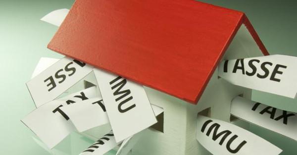 una casa giocattolo con il tetto rosso, all'interno alcuni pezzi di carta con srcitto IMU