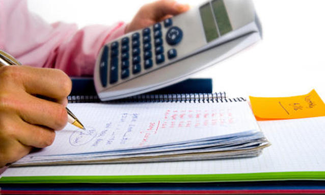 Un quaderno ad anelli con scritte, la punta di una penna ed una mano che regge una calcolatrice