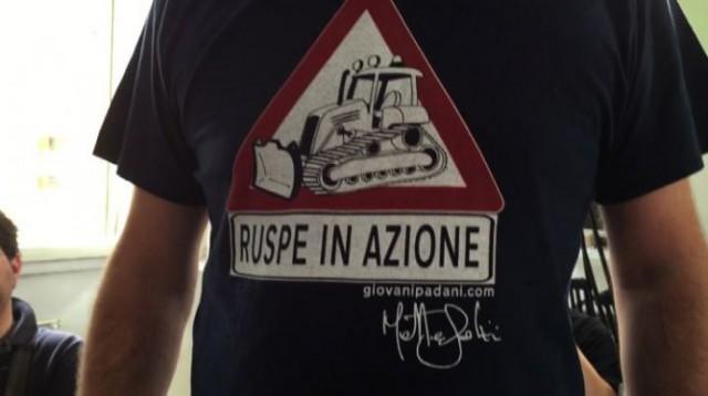 """Primo piano della maglietta di Salvini. Immagine di una ruspa all'interno di un segnale di attenzione, sotto la scritta """"ruspe in azione"""""""