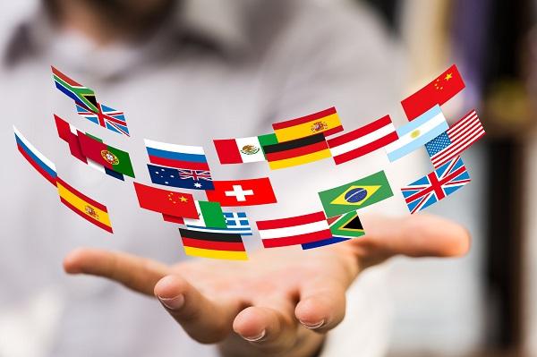 una mano con sopra la rappresentazione delle bandiere nazionali di molti paesi