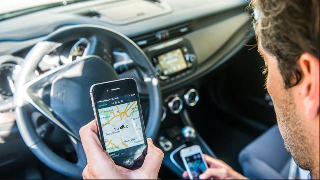 Uber, foto di cellulare e app uber in auto