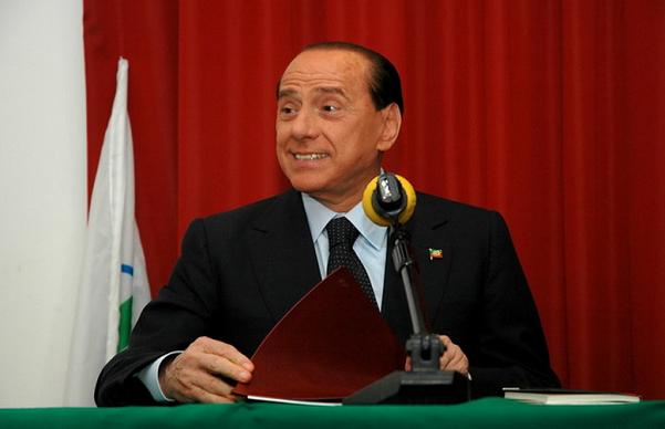 silvio berlusconi seduto mentre parla al microfono forza italia