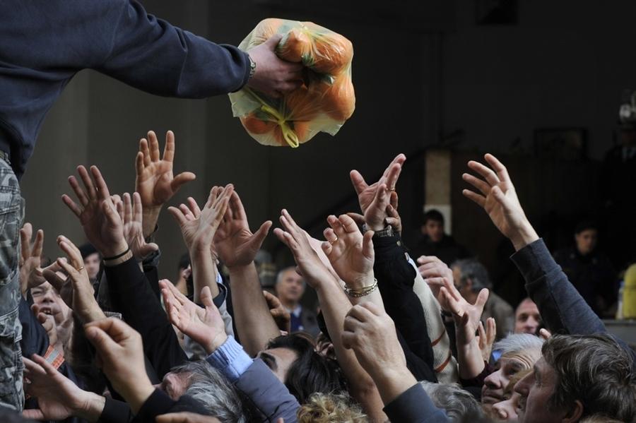 Persone che cercano di recuperare frutta e verdura distribuiti gratuitamente dagli agricoltori durante una protesta al di fuori del ministero dell'agricoltura, Atene, 6 febbraio 2013.