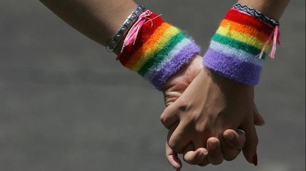mano nella mano con bracciali colore arcobaleno