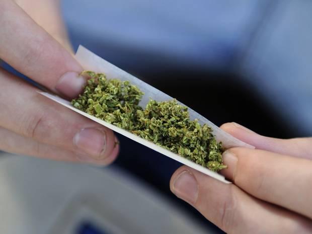 immagine di marijuana dentro una cartina con mani che la tengono tesa