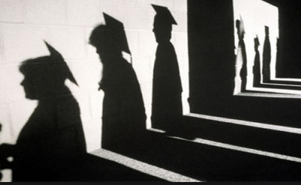 ombre di laureandi sul muro col cappello accademico