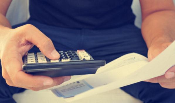 persona con calcolatrice e foglio in mano per conteggi pagamento arretrati canone rai