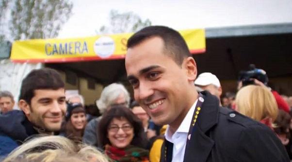 elezioni 4 marzo 2018, luigi di maio mentre parla ad imola con simpatizanti del movimento 5 stelle con alle sue spalle lo stand del gruppo m5s alla camera