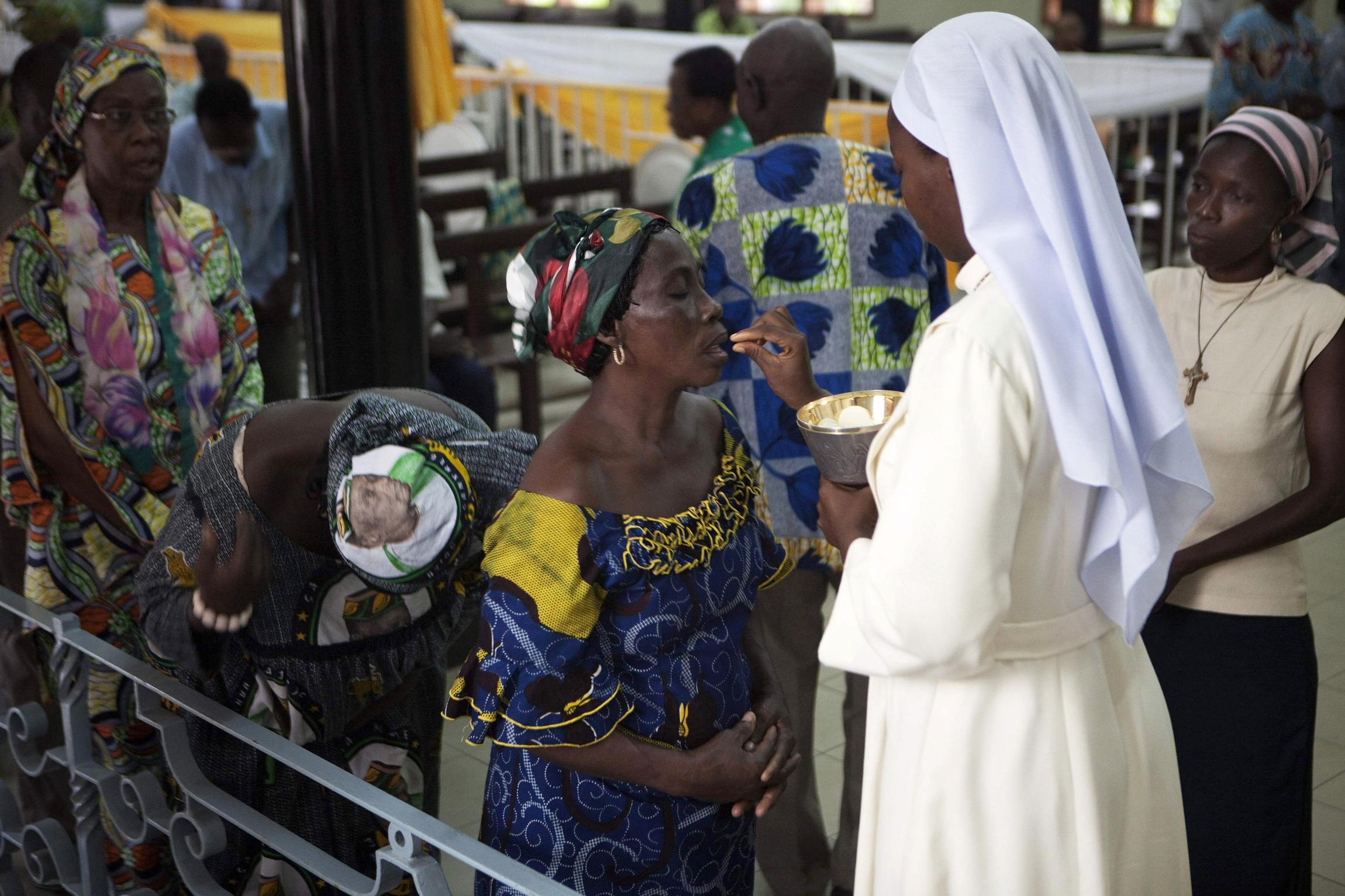 ricchezza Chiesa, donna nera riceve la comunione da una suora