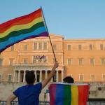 Diritti LGBT, Grecia, Italia, due persone con la bandiera dei diritti lgbt davanti ad un ministero greco