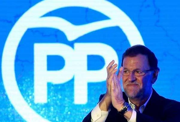Elezioni Spagna, Mariano Rajoy, Partito Popolare, il leader del PP mentre batte le mani e dietro il simbolo del Partito Popolare