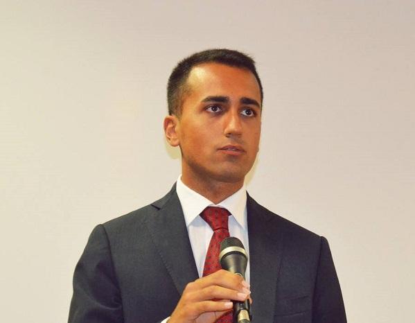 sondaggi m5s, di maio, movimento 5 stelle, il vicepresidente della camera con microfono in mano camicia bianca e cravatta rossa e sfondo chiaro