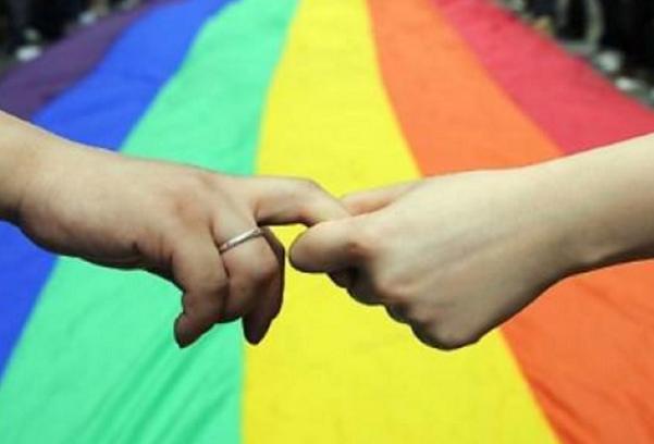 unioni civili, l'immagine di due mani che si avvicinano e sullo sfondo la bandiera coi colori arcobaleno