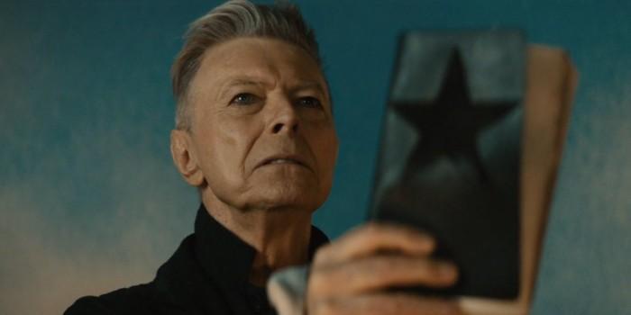 David Bowie che tiene in mano un libro con una Blackstar in copertina