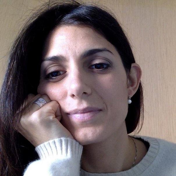 comunali Roma, Movimento 5 Stelle, la candidata in primo piano con una mano sotto il mento e maglione bianco