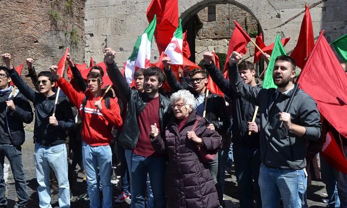 comunali Roma Alessandro Mustillo, candidato a sindaco di Roma per il Partito Comunista di Marco Rizzo tra le bandiere rosse e tricolore partigiani 25 aprile pugno chiuso