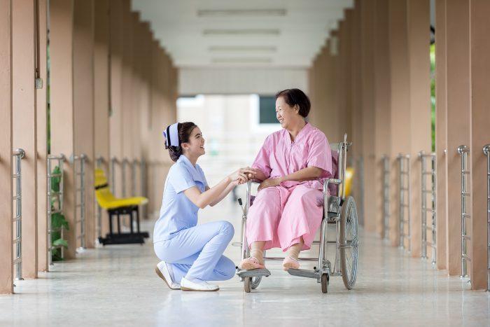 infermiera con una paziente in sedia a rotelle in ospedale, testamento biologico
