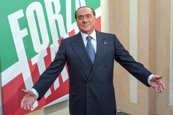 berlusconi a braccia aperte davanti alla bandiera di forza italia