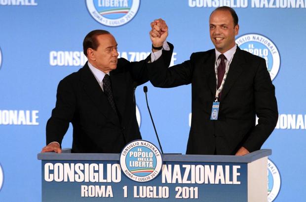Silvio Berlusconi ed Angelino Alfano si stringono la mano sul palco di un comizio del Popolo delle libertà. Sul poggio c'è la scritta Consiglio Nazionale Roma 1 luglio 2011 ed il logo del partito