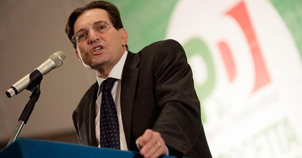 rosario crocetta parla al microfono in una conferenza. Sullo sfondo logo PD
