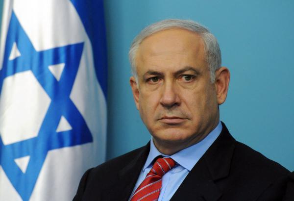 benjamin netanyahu in primo piano con di fianco bandiera israele