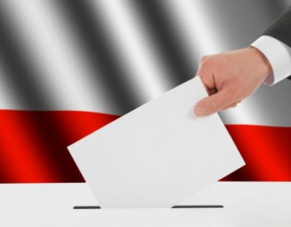 Elezioni, l'urna per le votazioni e sullo sfondo bandiera della Polonia